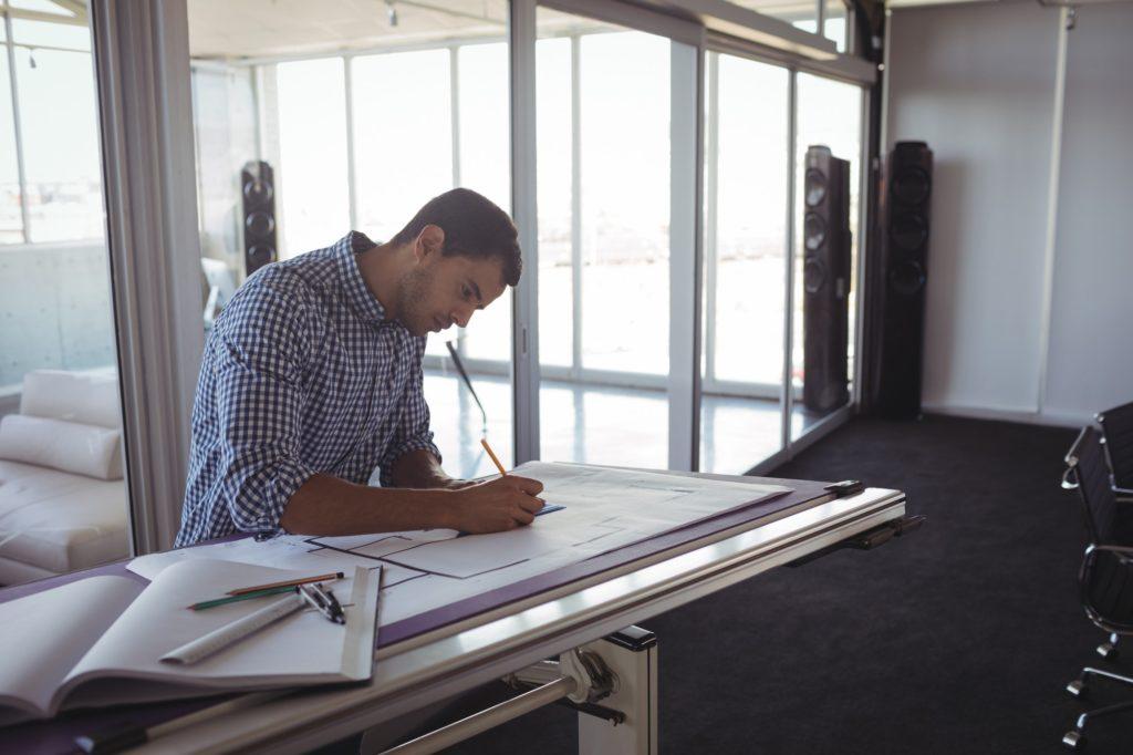 Serious interior designer planning on paper